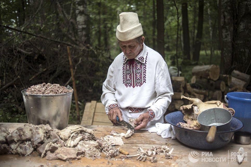 Житель села Шоруньжа во время приготовления ритуального яства на празднике Сярем.
