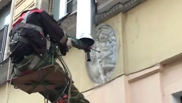 Стоп-кадр с видео, где рабочий сверлит барельеф с изображением ангела на фасаде дома №1 на Ропшинской улице в Санкт-Петербурге. 8 августа 2018