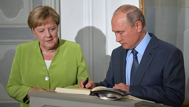 Президент РФ Владимир Путин оставляет запись в книге почетных гостей во время встречи с федеральным канцлером ФРГ Ангелой Меркель в резиденции правительства ФРГ Мезеберг. 18 августа 2018