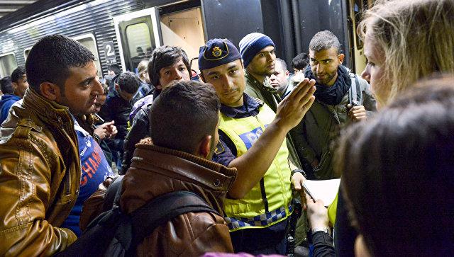 Сотрудник шведской полиции на вокзале в Стокгольме показывает дорогу мигрантам. Архивное фото