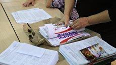Члены избирательной комиссии во время подсчета неиспользованных бюллетеней