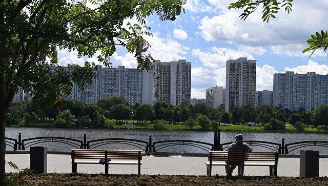 Мужчина сидит на лавочке на набережной Москвы-реки на территории парка 850-летия Москвы в районе Марьино
