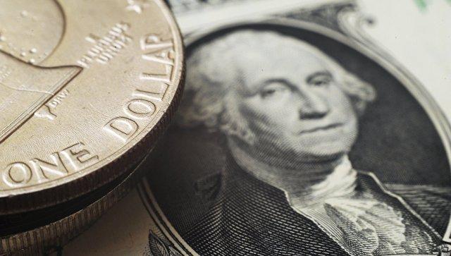 Монета номиналом один доллар США на банкноте один доллар США. Архивное фото