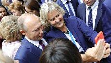 Президент РФ Владимир Путин фотографируется с участницей второго Евразийского женского форума в Таврическом дворце в Санкт-Петербурге. 20 сентября 2018