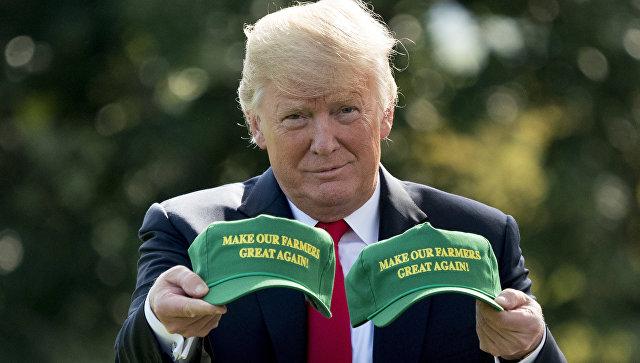 Президент США Дональд Трамп демонстрирует кепки с надписью Сделаем наших фермеров снова великими. Вашингтон, США
