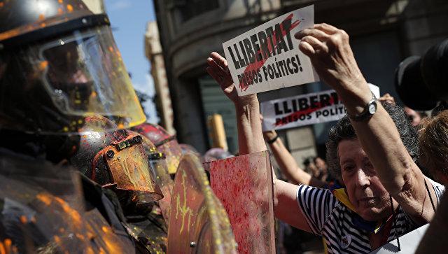 Женщина с плакатом Свободу политическим заключенным пред лицом полицейского на акции протеста в Барселоне. 29 сентября 2018