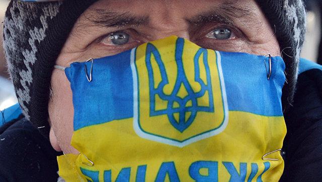Участник акции протеста в маске с изображением флага и герба Украины в Киеве. Архивное фото