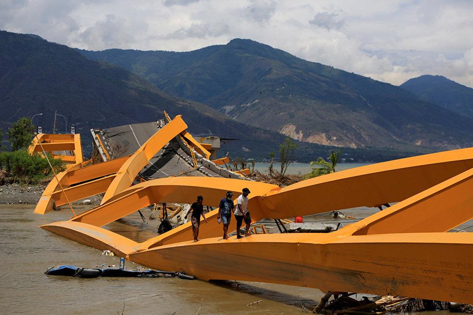 Люди идут по разрушенному мосту на острове Сулавеси, Индонезия