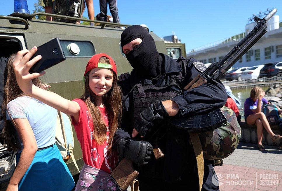 Девочка фотографируется с сотрудником полиции во время акции Курорт – 2015. Кубань – территория безопасности в Краснодарском крае