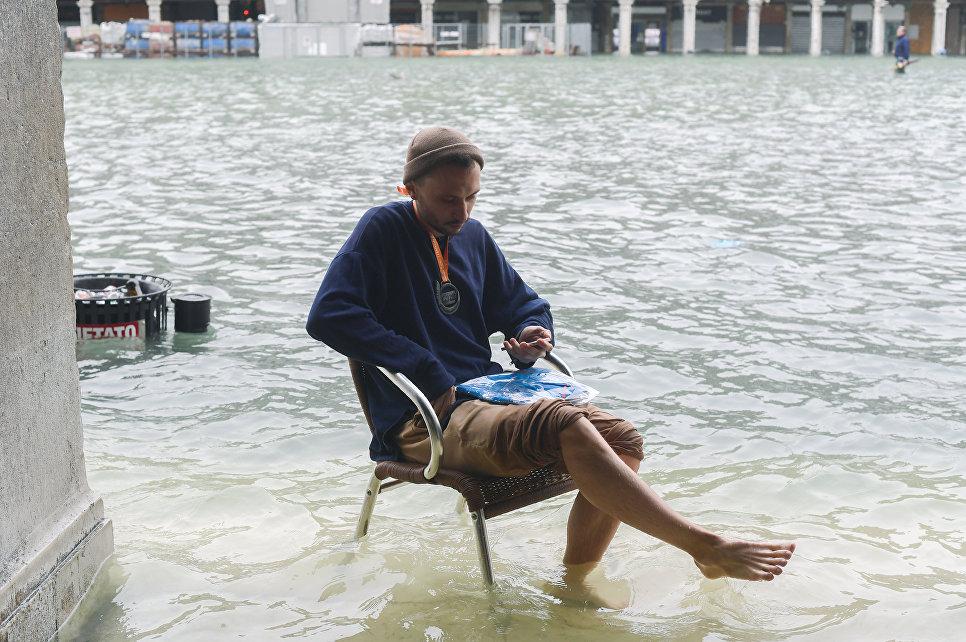 Мужчина на затопленной площади Святого Марка во время сезонного половодья в Венеции, Италия. 29 октября 2018 года