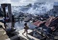 Девочка проходит мимо разрушенных домов после пожара, охватившего район трущоб в Навотасе, Филиппины. 8 ноября 2018 года