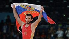 Российский борец Джамал Отарсултанов, завоевавший золотую медаль, с российским флагом после победы в финальном поединке