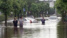 Японцы ходят по улицам затопленных городов по пояс в воде