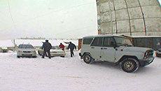 Полицейские вытягивают машины из снежных заносов в Магадане