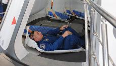 Сотрудник Роскосмоса демонстрирует пилотируемый космический корабль Русь на Десятом международном авиакосмическом салоне МАКС-2011.