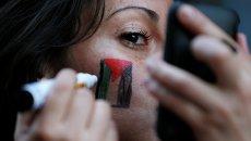 Девушка рисует на лице флаг Палестины