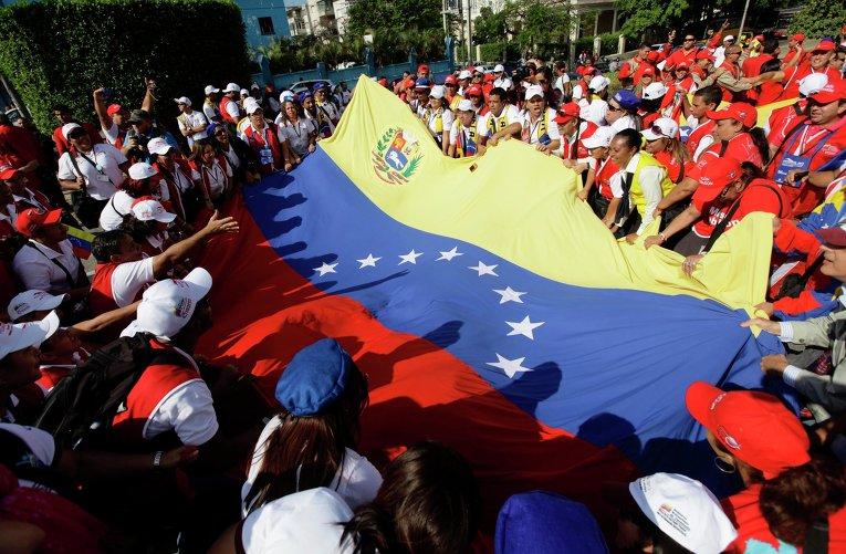 Венесуэльские студенты держат свой национальный флаг в знак поддержки президента Уго Чавеса в Гаване