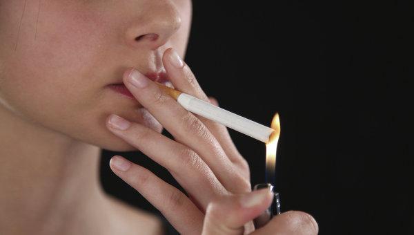 Женщина поджигает сигарету. Архивное фото