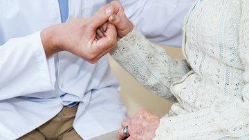 Врач держит пациентку за руку