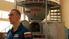 Космонавт Анатолий Иванишин на фоне тренажеракорабля