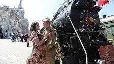 Молодые люди в одежде времен Великой Отечественной войны стоят у ретро-поезда Победа