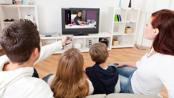 Молодая семья смотрит телевизор. Архивное фото