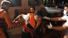 Спасатели помогали сойти на берег выжившим в кораблекрушении у Лампедузы