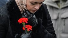 Женщина в международном аэропорту Казань несет цветы в память о погибших в авиакатастрофе самолета Boeing 737 авиакомпании Татарстан,