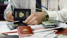 Сотрудник посольства проверяет паспорта российских граждан. Архив