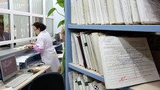 Медицинский работник выдает медицинскую карту пациенту в регистратуре районной поликлиники, архивное фото