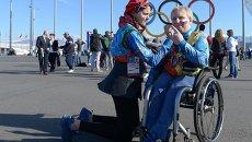 Волонтер в Олимпийском парке Сочи рисует на щеке болельщика российский флаг